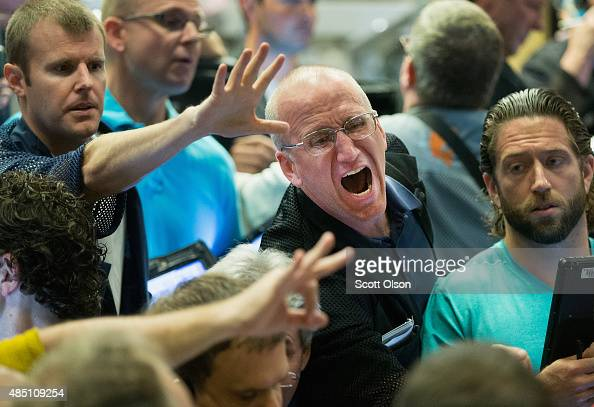 Traders signal offers in the Standard Poor's 500 stock index options pit at the Chicago Board Options Exchange on August 24 2015 in Chicago Illinois...