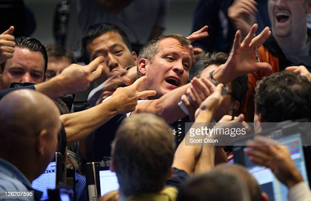 Traders signal offers on Standard Poor's 500 stock index options at the Chicago Board Options Exchange on September 23 2011 in Chicago Illinois US...