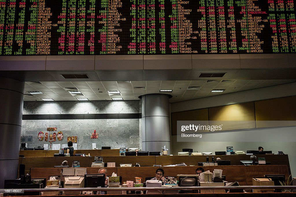 Traders sit at their desks beneath electronic stock boards in the trading gallery at the RHB Investment Bank Bhd. headquarters in Kuala Lumpur, Malaysia, on Monday, May 6, 2013. The biggest surge in Malaysian stocks since 2008 has turned into a money-losing day for investors who piled in at the height of the rally sparked by Prime Minister Najib Razak's election victory. Photographer: Sanjit Das/Bloomberg via Getty Images