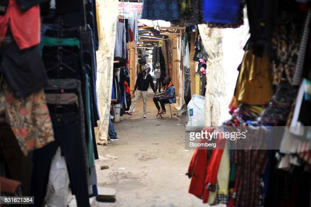 Traders sit in an alley between open and closed stores following post election unrest inside the Toi market in the outskirts of Kibera slum in...