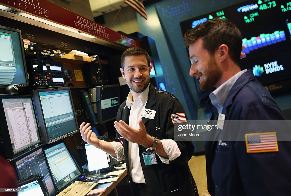 Traders smile on the floor of the New York Stock Exchange on July 13, 2012 in New York City. The Dow Jones Industrial Average rallied July 13, closing up almost 204 points to finish at 12,777. The rally ended a 6-day slump, the longest since mid-May.