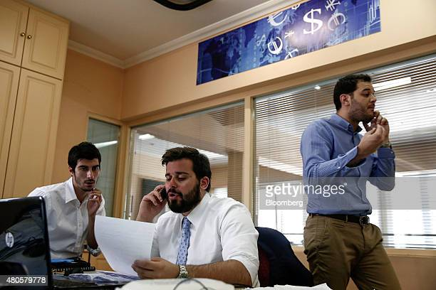 Traders speak on phones inside the offices of Nuntius Securities SA brokers in Athens Greece on Monday July 13 2015 Greece has been in financial...