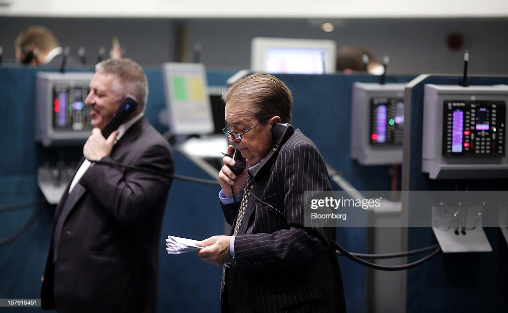 Traders speak on telephones as they work on the trading floor of the London Metal Exchange (LME) in London, U.K., on Friday, Dec. 7, 2012. The London Metal Exchange's $2.2 billion takeover by the Hong Kong Exchanges & Clearing Ltd. was completed yesterday. Photographer: Simon Dawson/Bloomberg via Getty Images