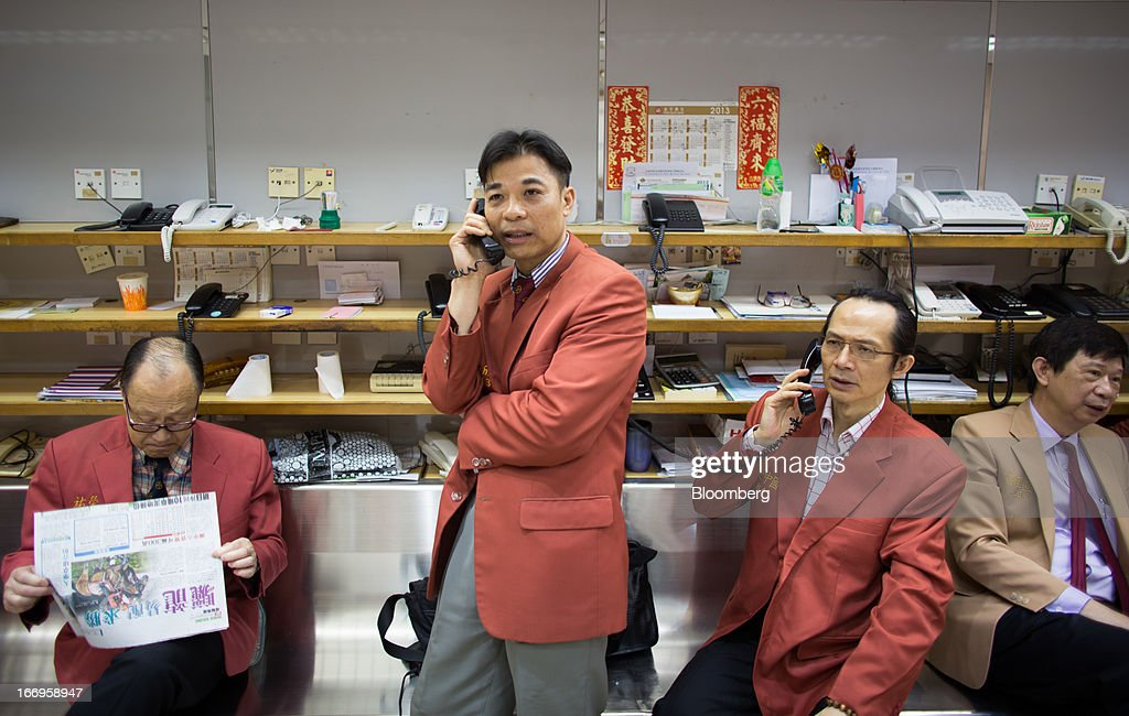 Traders speak on the telephone in the trading hall of The Chinese Gold and Silver Exchange Society in Hong Kong, China, on Friday, April 19, 2013. Gold traders are divided on whether bullion will extend declines after the biggest plunge in three decades generated buying from investors and jewelers. Photographer: Lam Yik Fei/Bloomberg via Getty Images