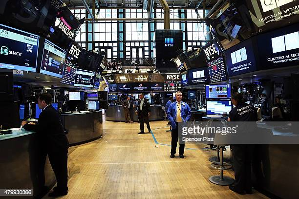 Traders stand on a nearly empty trading floor at the New York Stock Exchange after trading was halted due to a 'technical glitch' on July 8 2015 in...
