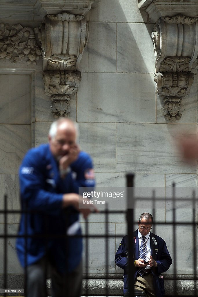 Traders stand outside the New York Stock Exchange during afternoon trading on August 10, 2011 in New York City. Stocks fell sharply again today after a major rebound yesterday.