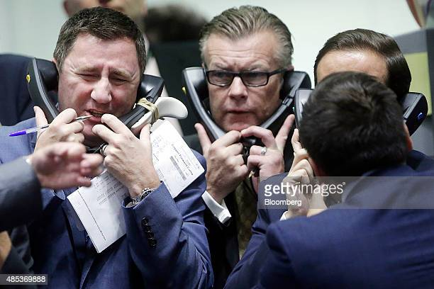 Traders use telephones as they work from the trading floor of the open outcry pit at the London Metal Exchange in London UK on Thursday Aug 27 2015...