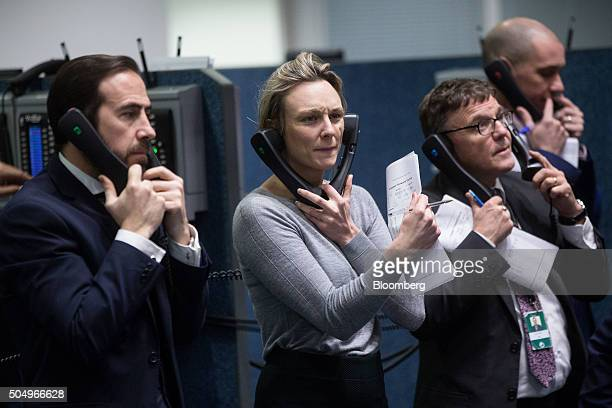 Traders use telephones as they work from the trading floor of the open outcry pit at the London Metal Exchange in London UK on Thursday Jan 14 2016...