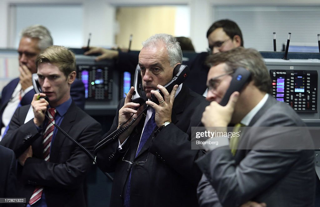 Traders use telephones as they work on the trading floor of the London Metal Exchange (LME) in London, U.K., on Wednesday, July 3, 2013. The London Metal Exchange's proposal to speed up deliveries of metal from its approved warehouses may lower aluminum and zinc premiums, Macquarie Group Ltd. said. Photographer: Chris Ratcliffe/Bloomberg via Getty Images