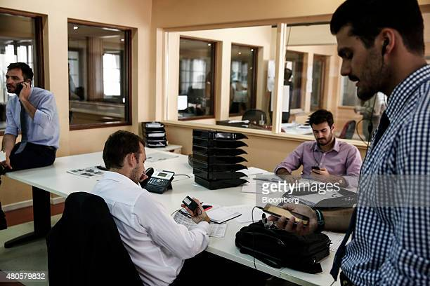 Traders use their mobile phones as they work inside the offices of Nuntius Securities SA brokers in Athens Greece on Monday July 13 2015 Greece has...