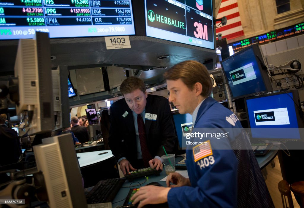 Traders view a monitor while working on the floor of the New York Stock Exchange (NYSE) in New York, U.S., on Wednesday, Jan. 2, 2013. U.S. stocks rose, after the largest year-end rally for the Standard & Poor's 500 Index since 1974, as lawmakers passed a bill averting spending cuts and tax increases threatening a recovery in the world's biggest economy. Photographer: Scott Eells/Bloomberg via Getty Images