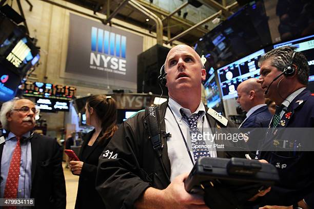 Traders wait for trading to resume on the floor of the New York Stock Exchange after trading was halted due to a 'technical glitch' on July 8 2015 in...