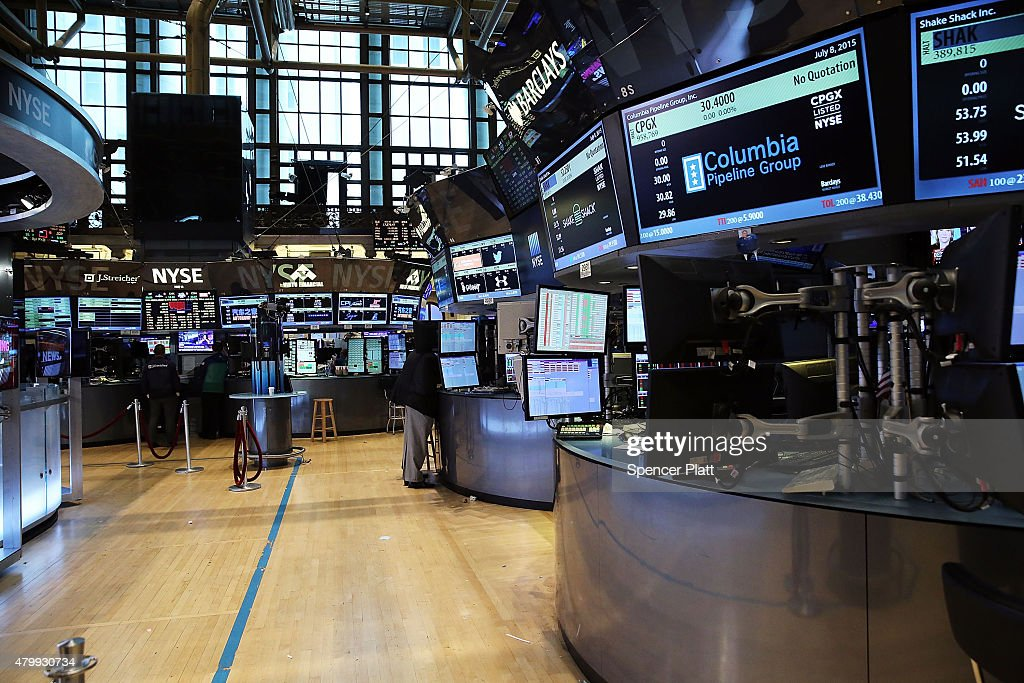 Traders wait on a nearly empty trading floor at the New York Stock Exchange after trading was halted due to a 'technical glitch' on July 8 2015 in...