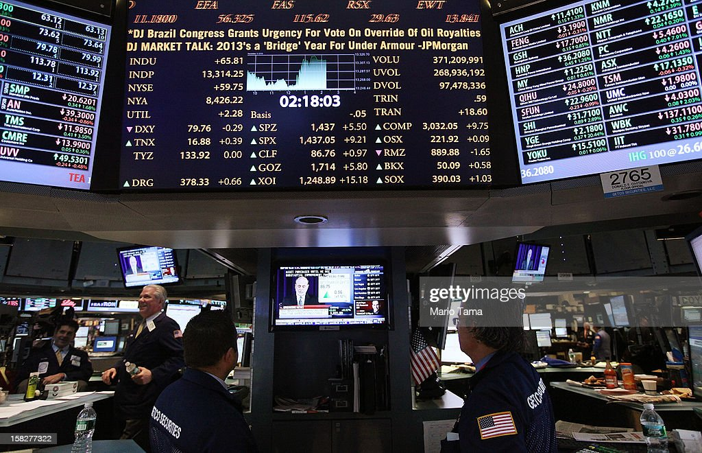 Traders (BOTTOM C) watch as Federal Reserve Chairman Ben Bernanke's press conference is broadcasted on the floor of the New York Stock Exchange on December 12, 2012 in New York City. Bernanke announced the Federal Reserve will tie its bond purchase program to the rate of the nation's unemployment.