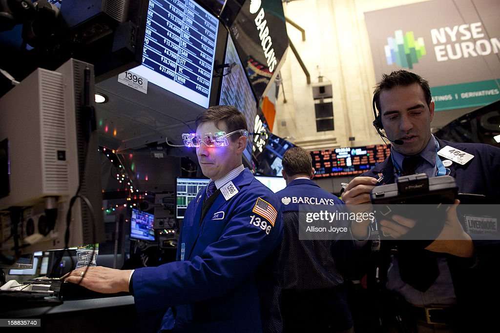 Traders wear 2013 New Years party glasses while they work on the floor of the New York Stock Exchange December 31, 2012 in New York City. US lawmakers are struggling to work out a last-minute deal to avoid the 'fiscal cliff,' which could mean tax raises for millions of Americans.