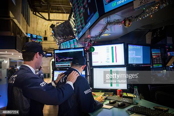 Traders wear hats that say 'DOW 18000' as they work on the floor of the New York Stock Exchange during the afternoon of December 23 2014 in New York...