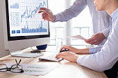 Team of traders working with forex (foreign exchange) trading charts and graphs on computer screen, concept about stock market investment, finance, selling and buying