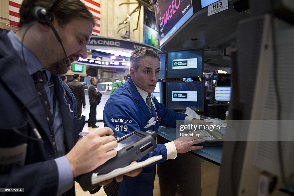 Traders work at the New York Stock Exchange (NYSE) in New York, U.S., on Friday, March 15, 2013. U.S. stocks fell, sending the Dow Jones Industrial Average lower for the first time in 11 days, as a report showed consumer confidence unexpectedly fell in March. Photographer: Scott Eells/Bloomberg via Getty Images