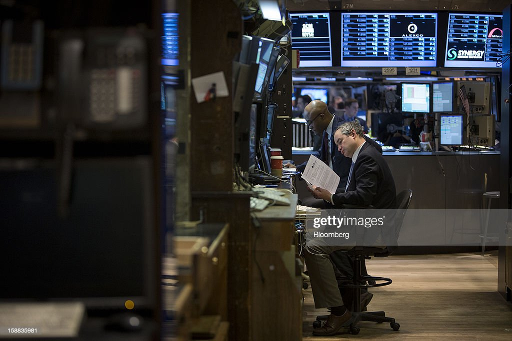 Traders work at the New York Stock Exchange (NYSE) in New York, U.S., on Monday, Dec. 31, 2012. Most U.S. stocks gained, rebounding from a five-day slump, as investors weighed prospects for a compromise in federal budget talks. Photographer: Scott Eells/Bloomberg via Getty Images