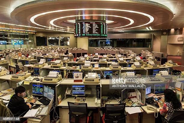 Traders work at the stock exchange in Hong Kong on April 9 2015 Hong Kong stocks surged 270 percent on April 9 chalking up gains of more than six...