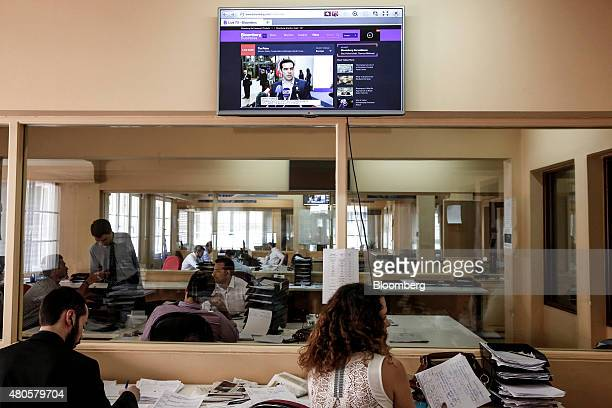Traders work beneath a television screen displaying a broadcast of Alexis Tsipras Greece's prime minister from Brussels inside the offices of Nuntius...