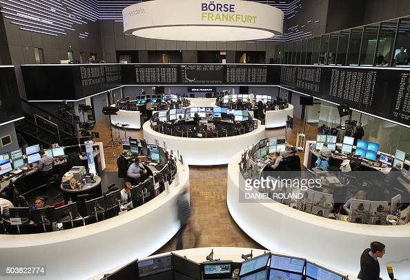 Traders work in front of a board displaying the chart of Germany's share index DAX at the stock exchange in Frankfurt am Main western Germany on...