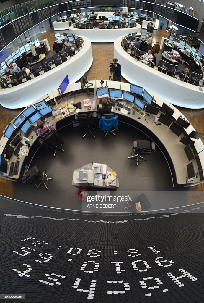 Traders work in front of a display showing the German share index DAX at the stock exchange in Frankfurt am Main, western Germany on October 25, 2013. Germany's DAX share index set a new all-time high when it briefly topped 9,000 points.