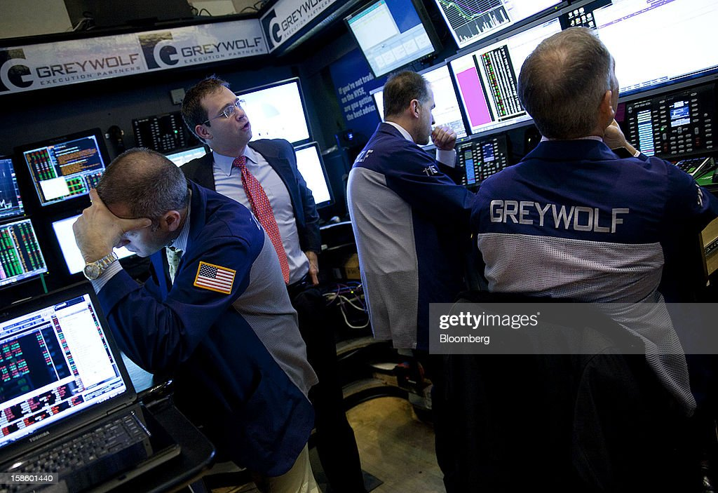 Traders work in the Greywolf Execution Partners booth on the floor of the New York Stock Exchange (NYSE) in New York, U.S., on Thursday, Dec. 20, 2012. InterContinentalExchange Inc. (ICE), the 12-year-old energy and commodity futures bourse, agreed to acquire NYSE Euronext for cash and stock worth $8.2 billion, moving to take control of the world's biggest equities market. Photographer: Jin Lee/Bloomberg via Getty Images