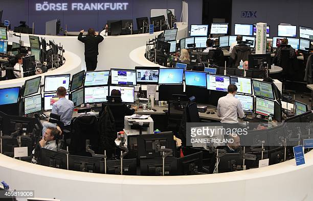 Traders work on December 2 2014 at the German Stock Exchange in Frankfurt am Main western Germany Germany's share index DAX exceeded the threshold of...