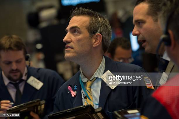 Traders work on the floor at the closing bell of the Dow Industrial Average at the New York Stock Exchange on August 8 2017 in New York Wall Street...
