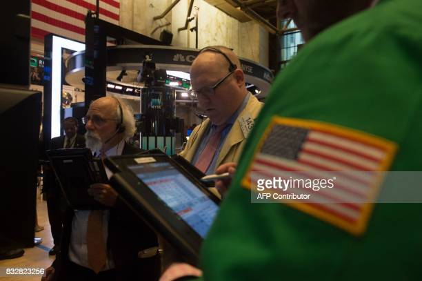Traders work on the floor at the closing bell of the Dow Industrial Average at the New York Stock Exchange on August 16 2017 in New York Wall Street...