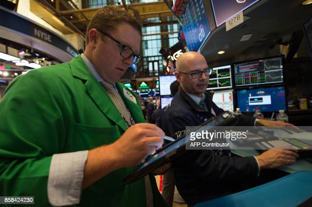 Traders work on the floor at the closing bell of the Dow Industrial Average at the New York Stock Exchange on October 6 2017 in New York Wall Street...