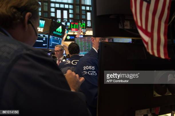 Traders work on the floor at the closing bell of the Dow Industrial Average at the New York Stock Exchange on October 13 2017 in New York / AFP PHOTO...