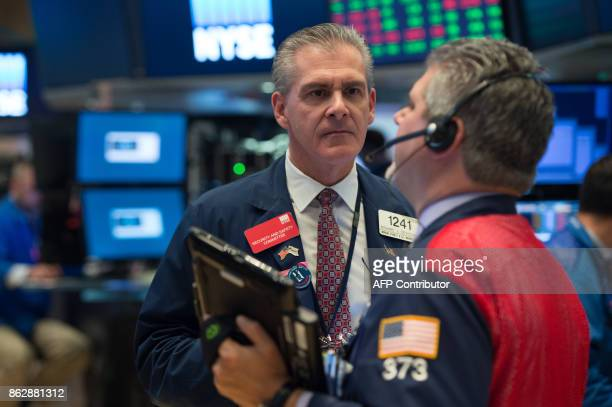 Traders work on the floor at the closing bell of the Dow Industrial Average at the New York Stock Exchange on October 18 2017 in New York The Dow...