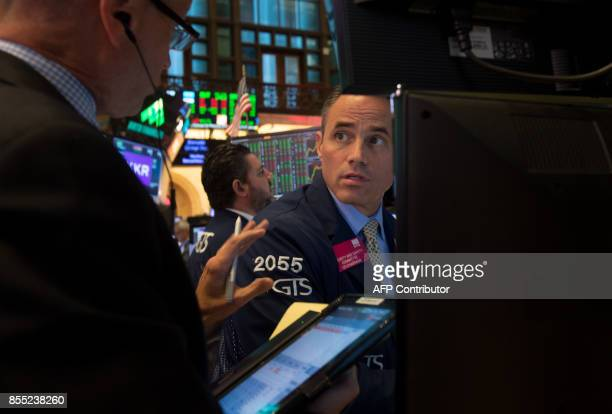 Traders work on the floor at the closing bell of the Dow Jones Industrial Average at the New York Stock Exchange on September 28 2017 in New York /...