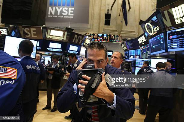 Traders work on the floor of the New York Stock Exchange a day after the market closed for over three hours yesterday due to a 'technical glitch' on...