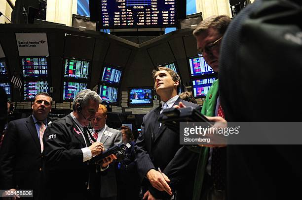 Traders work on the floor of the New York Stock Exchange after the opening bell in New York US on Thursday Oct 14 2010 US stocks fell dragging...