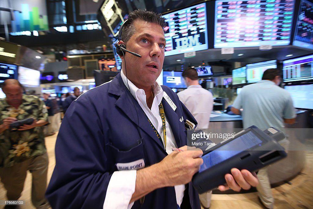 Traders work on the floor of the New York Stock Exchange after the closing bell on August 15, 2013 in New York City. Stocks dropped on weak earnings as the Dow fell 225 points to close at 15,112.19.