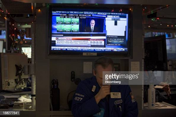 Traders work on the floor of the New York Stock Exchange as Ben S Bernanke chairman of the US Federal Reserve speaks on television in New York US on...