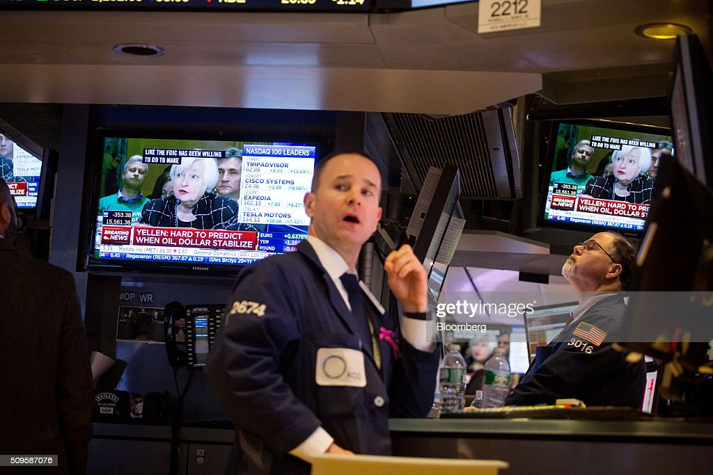 Traders work on the floor of the New York Stock Exchange (NYSE) as Janet Yellen, chair of the U.S. Federal Reserve, is seen speaking on a television screen in New York, U.S., on Thursday, Feb. 11, 2016. Global equities tumbled toward a bear market, with the Dow Jones Industrial Average plunging to 400 points, as financial markets signaled that investors have lost faith in central banks' ability to support the worldwide economy. Photographer: Michael Nagle/Bloomberg via Getty Images