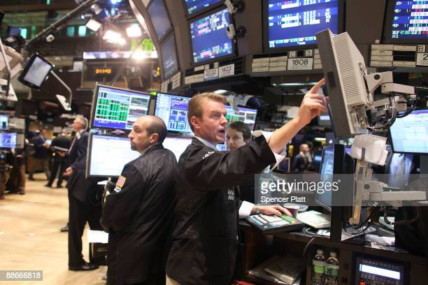 Traders work on the floor of the New York Stock Exchange as the Federal Reserve announces that it will be keeping its key interest rate near zero on...