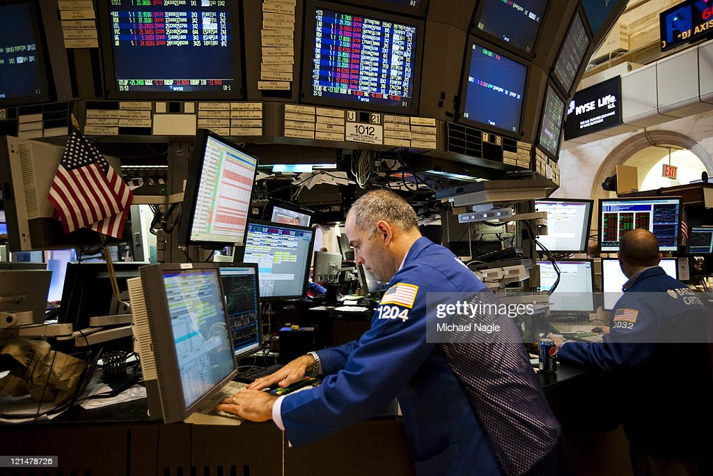 Traders work on the floor of the New York Stock Exchange before the closing bell on August 19, 2011 in New York City. The Dow ends another volatile week, closing more than 100 points down for the day.