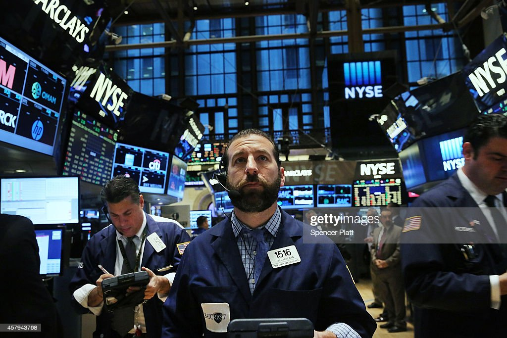 Traders work on the floor of the New York Stock Exchange during morning trading on October 27 2014 in New York City Stocks were lower in morning...