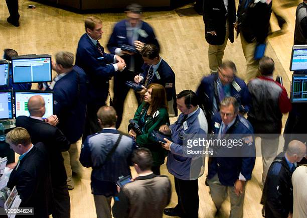 Traders work on the floor of the New York Stock Exchange in New York US on Friday July 16 2010 US stocks slid wiping out a weekly advance as revenue...