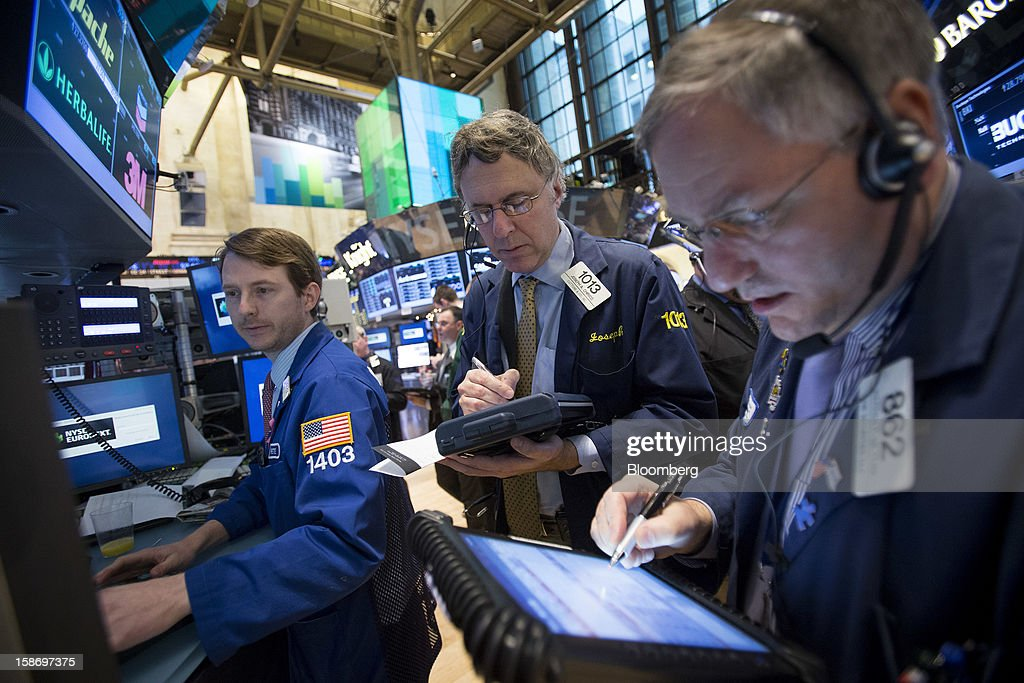 Traders work on the floor of the New York Stock Exchange (NYSE) in New York, U.S., on Monday, Dec. 24, 2012. Americans have missed out on almost $200 billion of stock gains as they drained money from the market in the past four years, haunted by the financial crisis. Photographer: Scott Eells/Bloomberg via Getty Images