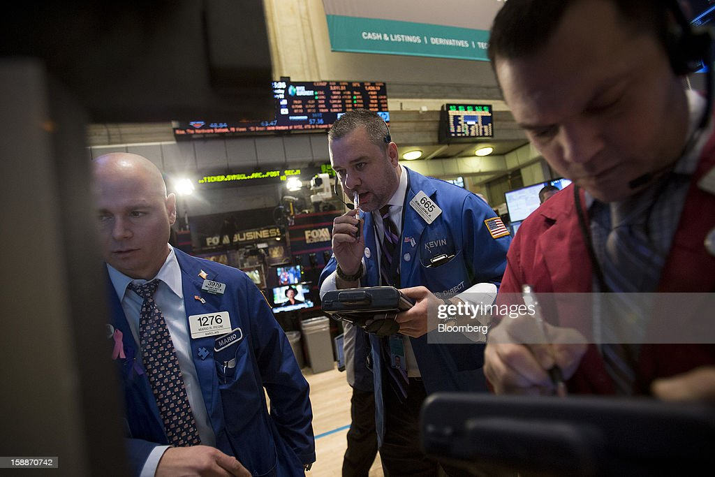 Traders work on the floor of the New York Stock Exchange (NYSE) in New York, U.S., on Wednesday, Jan. 2, 2013. U.S. stocks rose, after the largest year-end rally for the Standard & Poor's 500 Index since 1974, as lawmakers passed a bill averting spending cuts and tax increases threatening a recovery in the world's biggest economy. Photographer: Scott Eells/Bloomberg via Getty Images