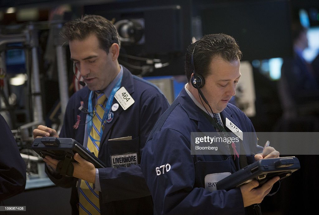Traders work on the floor of the New York Stock Exchange (NYSE) in New York, U.S., on Monday, Jan. 7, 2013. U.S. stocks fell, after the Standard & Poor's 500 Index climbed to a five-year high, as investors awaited the start of the corporate earnings season tomorrow. Photographer: Scott Eells/Bloomberg via Getty Images