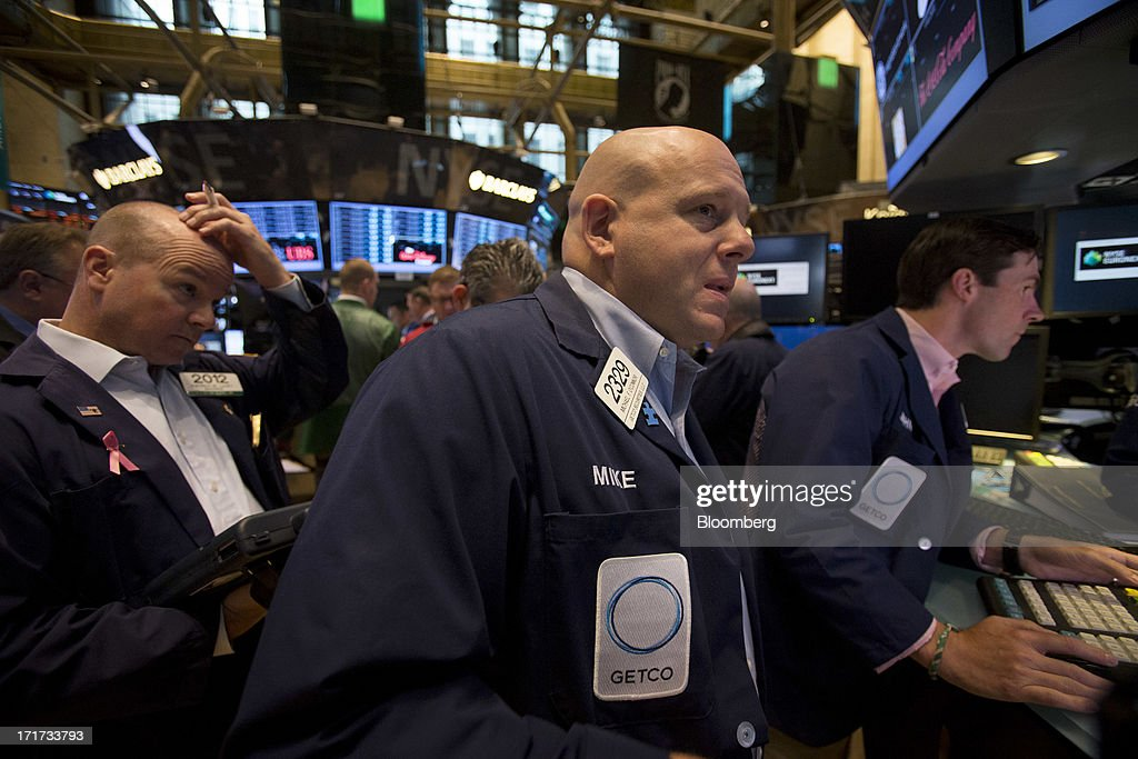 Traders work on the floor of the New York Stock Exchange (NYSE) in New York, U.S., on Friday, June 28, 2013. U.S. stocks fell, after the biggest three-day rally since January for the Standard & Poorâs 500 Index, before data on consumer sentiment and business activity as investors weighed statements from Federal Reserve officials. Photographer: Scott Eells/Bloomberg via Getty Images