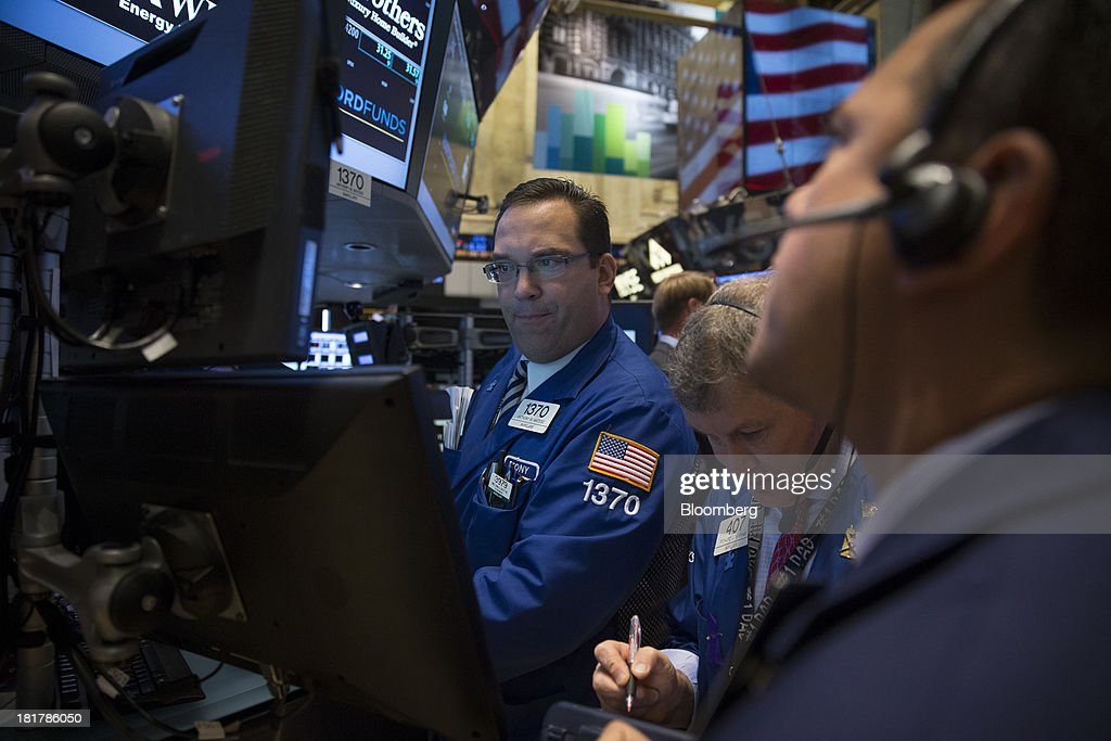 Traders work on the floor of the New York Stock Exchange (NYSE) in New York, U.S., on Wednesday, Sept. 25, 2013. U.S. stocks fluctuated, after the Standard & Poor's 500 Index fell four straight days, as investors weighed data on home sales amid growing concern that lawmakers won't reach a budget deal. Photographer: Scott Eells/Bloomberg via Getty Images
