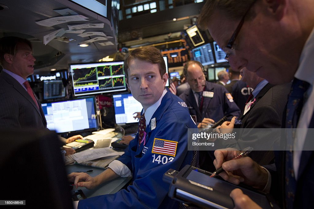 Traders work on the floor of the New York Stock Exchange (NYSE) in New York, U.S., on Thursday, Oct. 17, 2013. U.S. stocks fell, after the Standard & Poor's 500 Index came within four points of a record, as investors assessed the effects of the budget standoff and International Business Machines Corp. and Goldman Sachs Group Inc. tumbled amid declining revenues. Photographer: Scott Eells/Bloomberg via Getty Images